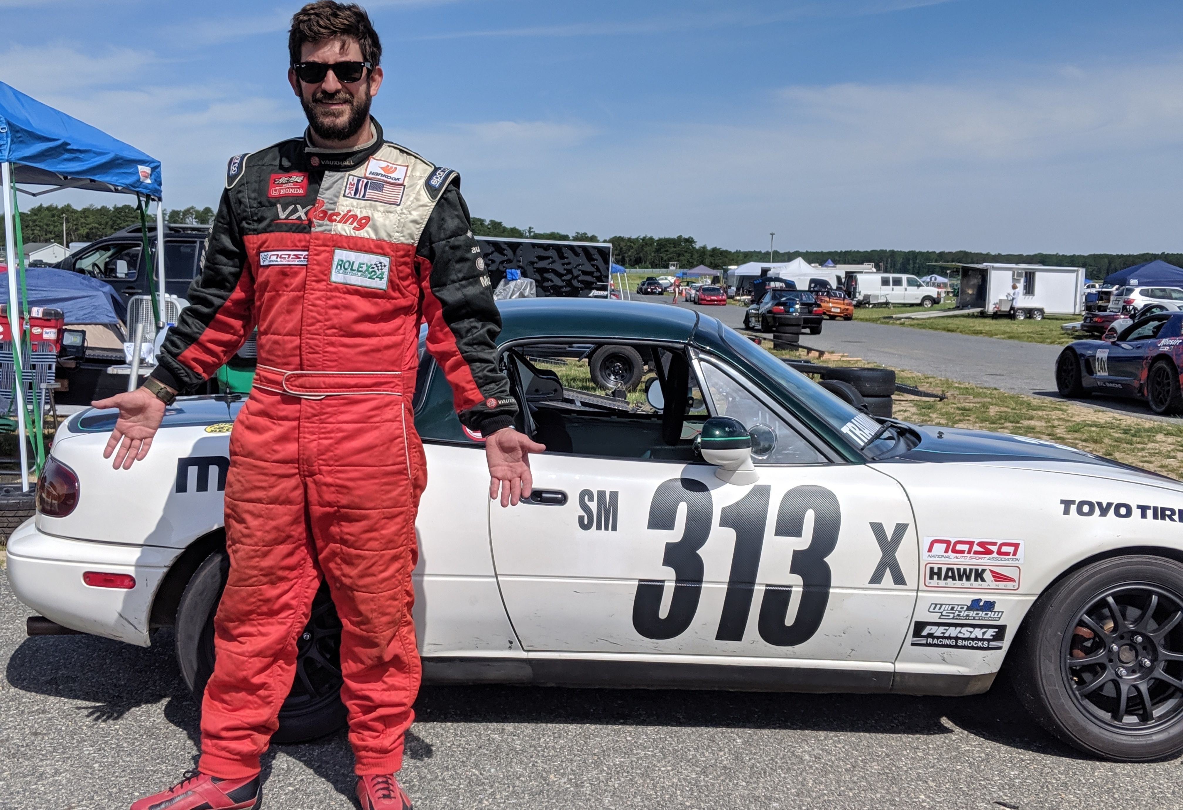 Race Driver in firesuit standing before Spec Miata Racecar